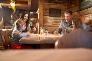 famile-beim-essen-in-uriger-hütte